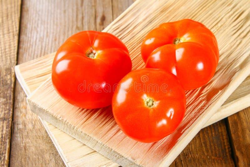 与叶子的新鲜的蕃茄在一张老木桌上 图库摄影