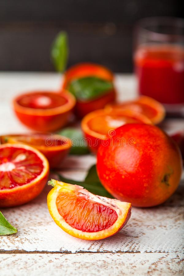 与叶子的血淋淋的红色桔子切片在木背景 免版税库存照片