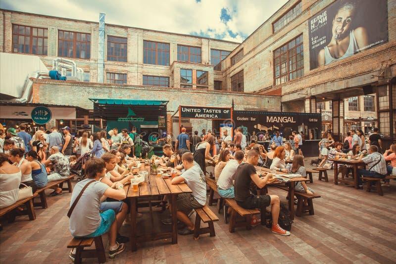 与吃和喝在室外街道食物节日期间的友好的党人民的许多桌 库存照片