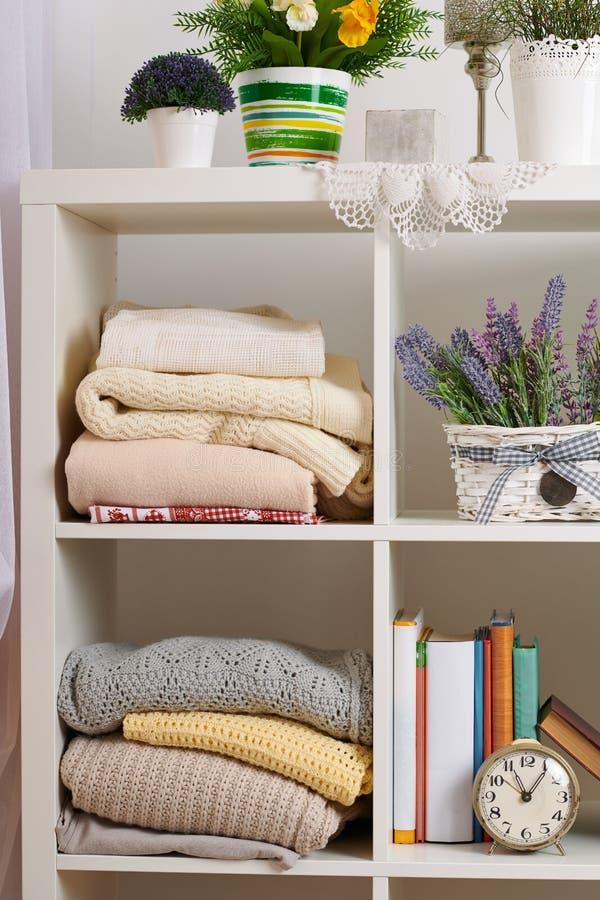 与各种各样的事在屋子里-书,手表,花,被编织的毯子的架子 库存照片