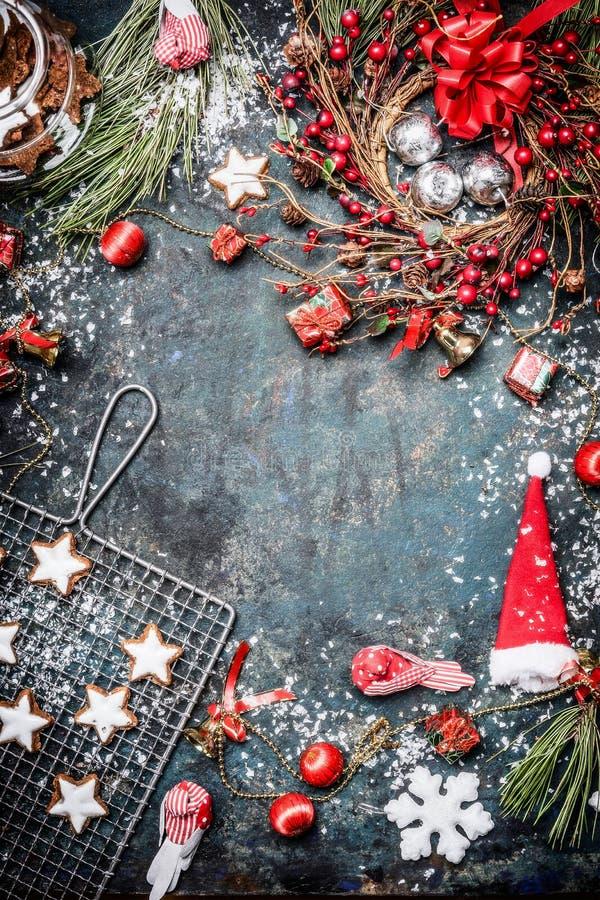 与各种各样的冬天装饰、曲奇饼、雪和花圈的圣诞卡在葡萄酒蓝色背景 库存图片