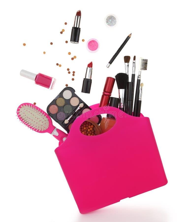 与各种各样的化妆用品的桃红色购物袋 免版税库存照片