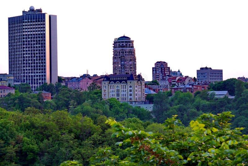与各种各样的建筑学站立的高层建筑物的城市处所反对绿色树背景的在的 库存照片