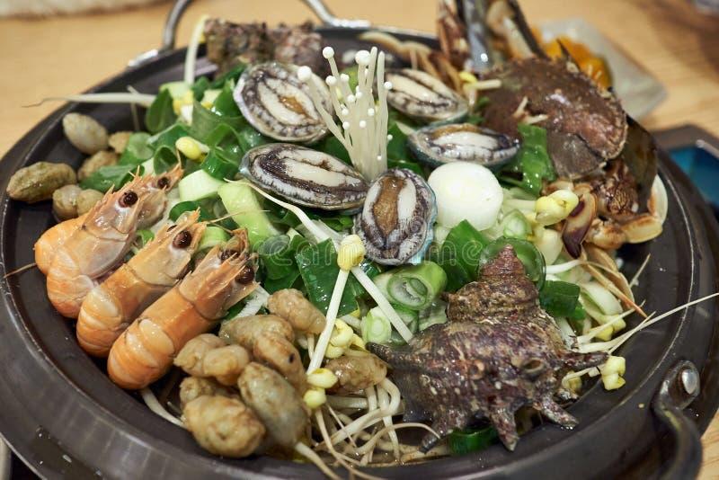 与各种各样的成份的热的韩国海鲜炖煮的食物包括虾、avalons、喇叭壳、有疣的水喷射器和菜 库存照片