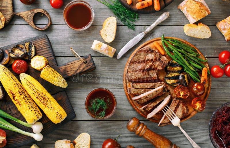 与各种各样的烤菜的水多的切的烤牛排 免版税图库摄影