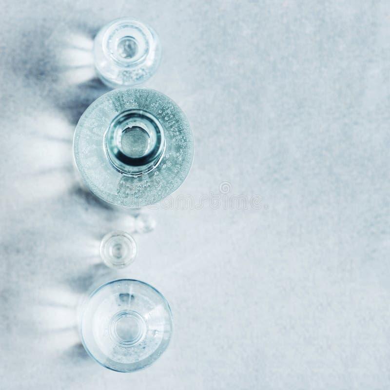 与各种各样的玻璃瓶和强光的织地不很细灰色背景  免版税图库摄影