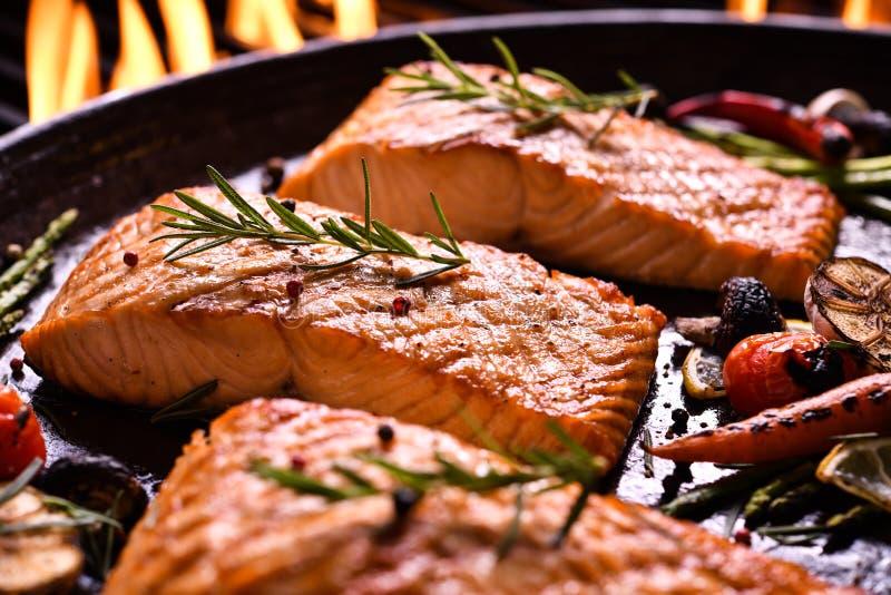 与各种各样的菜的烤三文鱼鱼在平底锅 免版税图库摄影