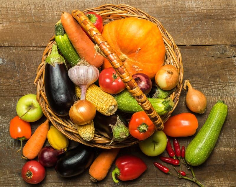 与各种各样的菜的篮子在土气木背景 免版税库存图片