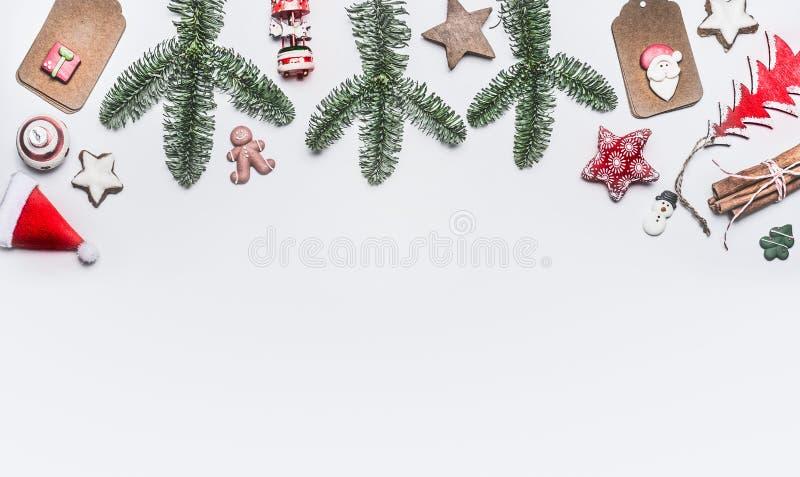 与各种各样的装饰的白色圣诞节快乐背景,冷杉分支和曲奇饼,与拷贝空间的顶视图 库存图片