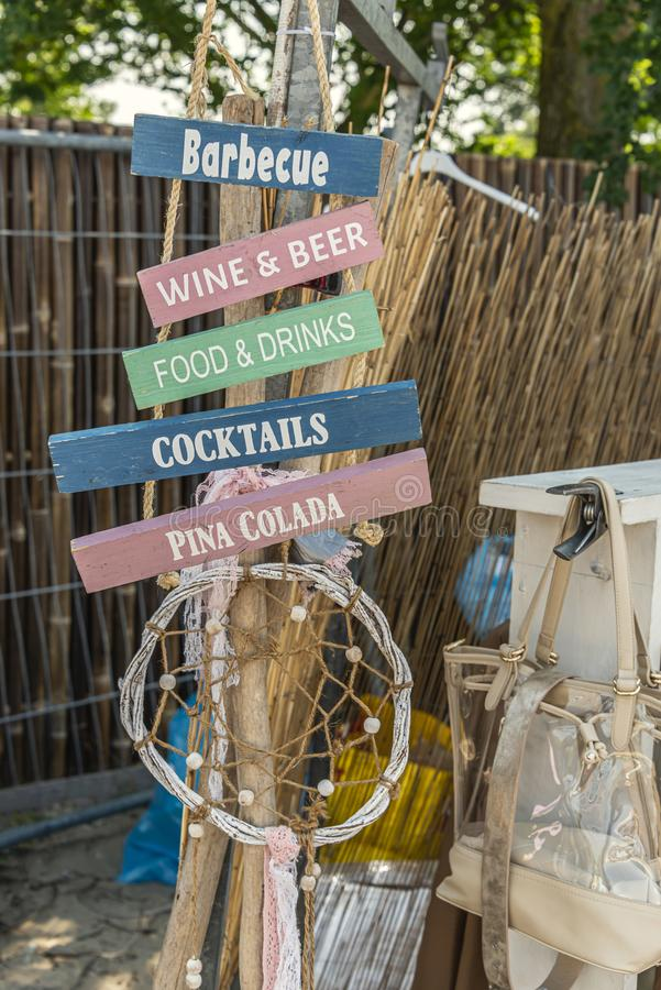 与各种各样的饮料和垂悬在绳索的食物文本的牌 库存照片