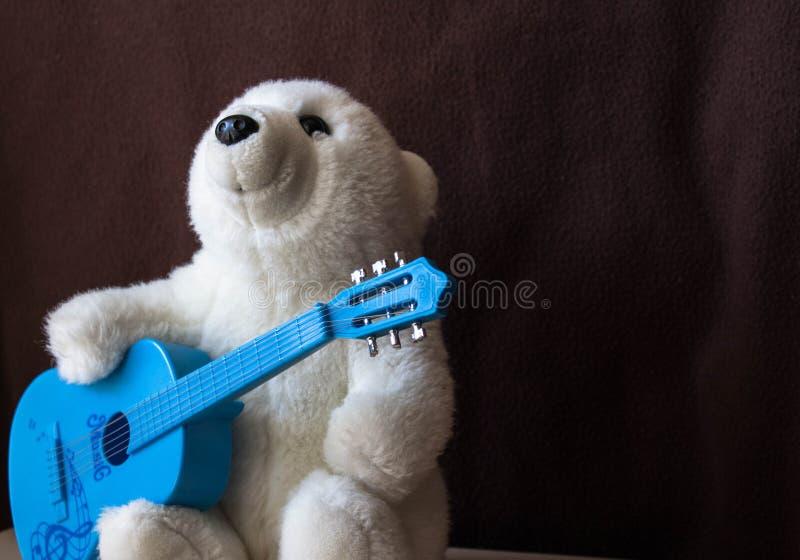 与吉他的一头北极熊在黑背景 库存图片