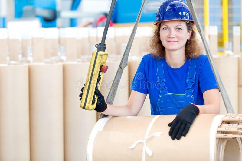 与吊车的工厂劳工移动的变压器卷 库存照片