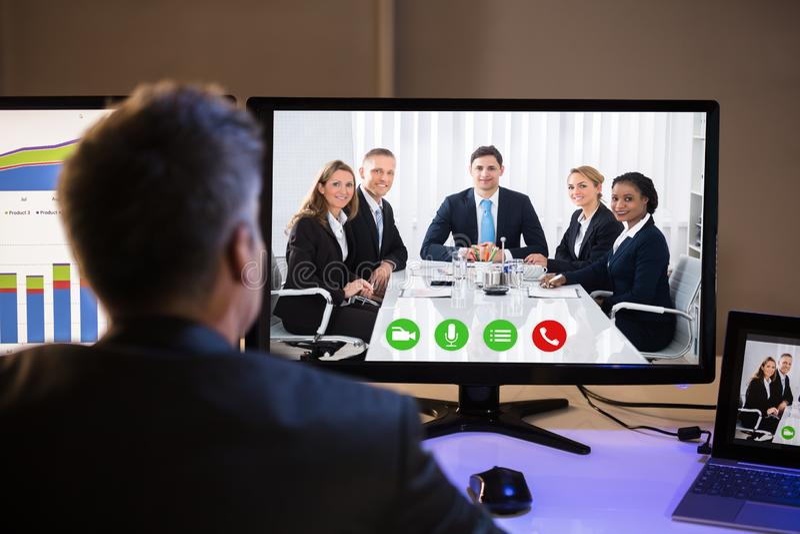 与同事的商人视讯会议在计算机上 库存照片