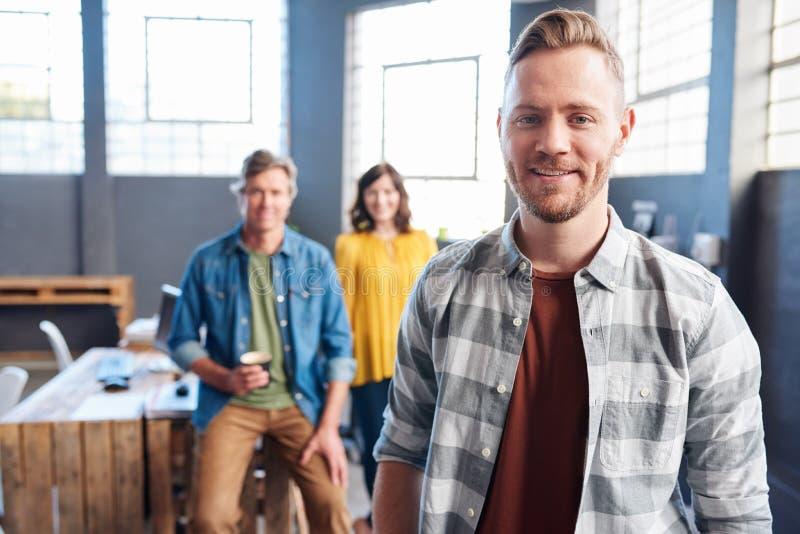 与同事的微笑的年轻商人在背景中 免版税库存照片