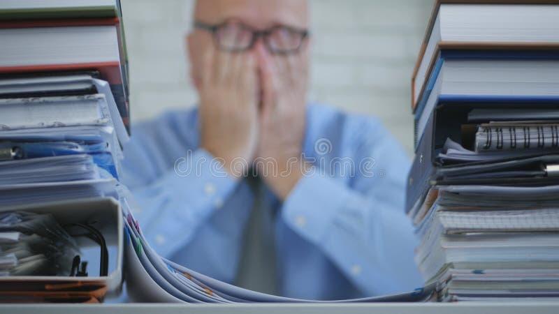 与后工作在会计办公室的疲乏的商人的模糊的照片 库存照片
