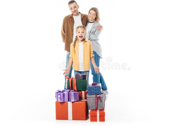 与后边堆的激动的孩子被包裹的礼物和父母 库存图片
