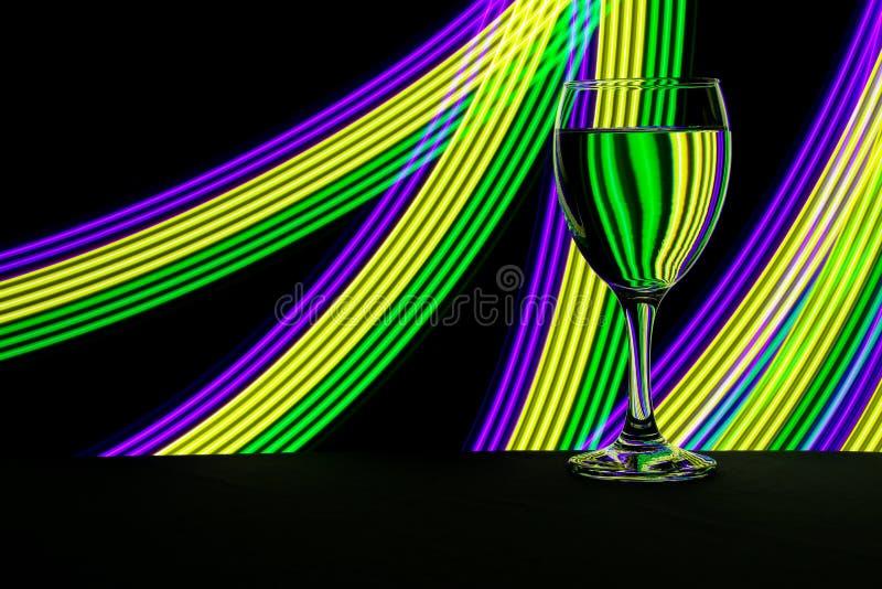 与后边霓虹灯的酒杯 免版税库存图片