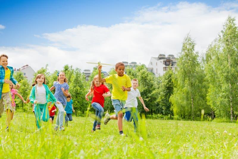 与后边飞机玩具和孩子的非洲孩子 免版税库存图片