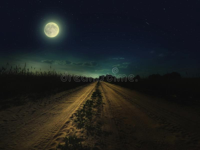 与后退入与绿草的距离的fullmoon的美丽的不可思议的夜空和星和路 免版税库存图片