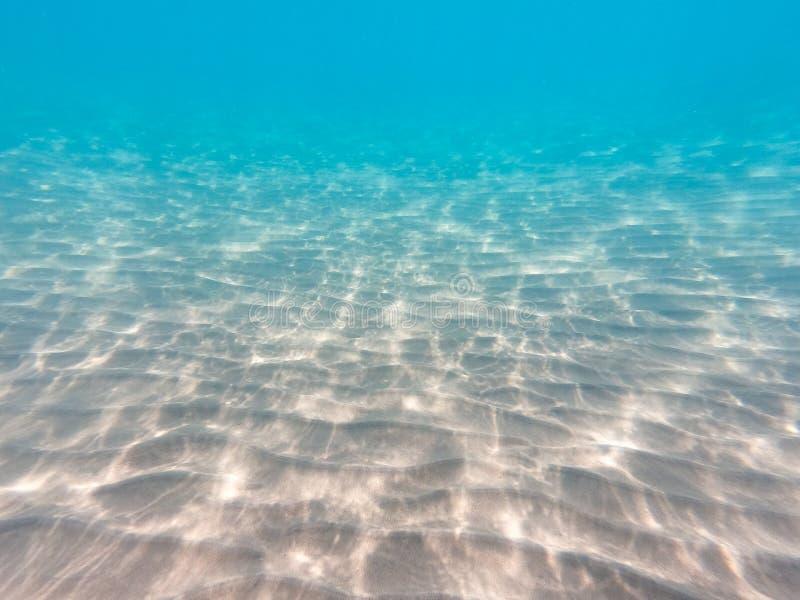 与含沙海底的水下的背景 海和海洋水的美好的纹理 纯净的水纹理 免版税库存图片