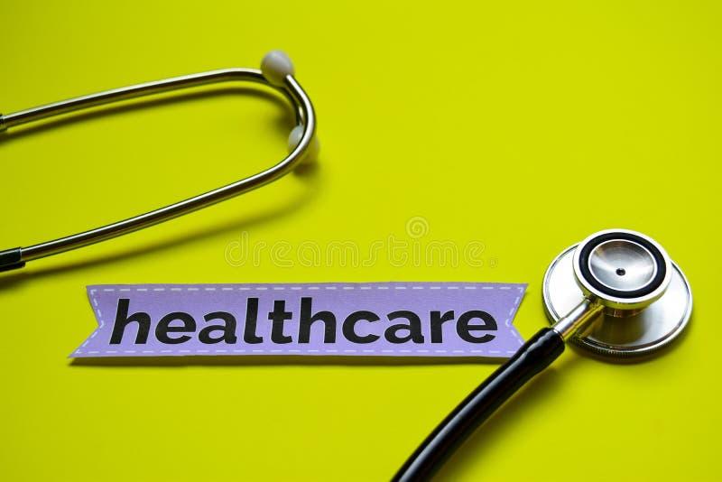 与听诊器概念启发的医疗保健在黄色背景 图库摄影
