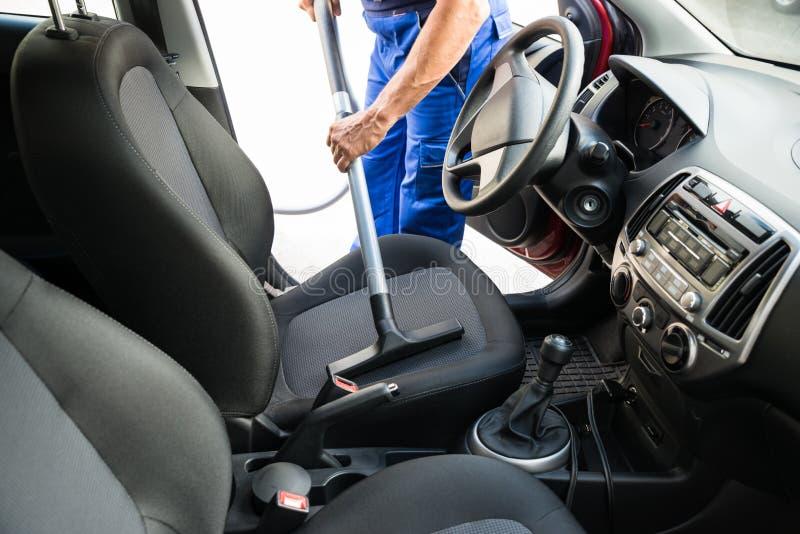 与吸尘器的人吸尘的汽车座位 库存图片
