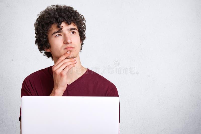 与周道卷发、举行在旁边下巴和神色的沉思年轻男性,为做介绍使用现代便携式计算机, 库存照片