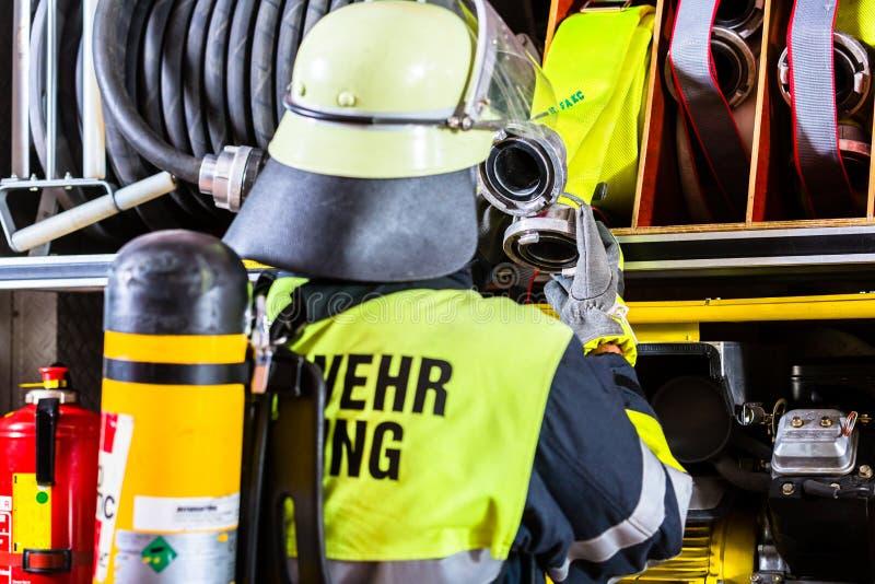 与呼吸的保护和氧气罐的消防队员 免版税库存照片