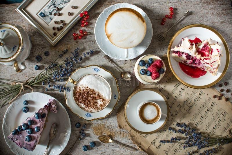 与咖啡、蛋糕、杯形蛋糕、曲奇饼、cakepops、点心、果子、花和新月形面包装载的表  古老匙子和tra 库存照片