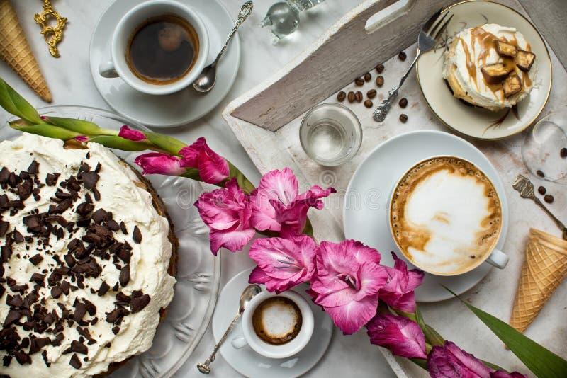 与咖啡、蛋糕、杯形蛋糕、点心、果子、花和新月形面包装载的表  古老匙子和盘子, 库存图片