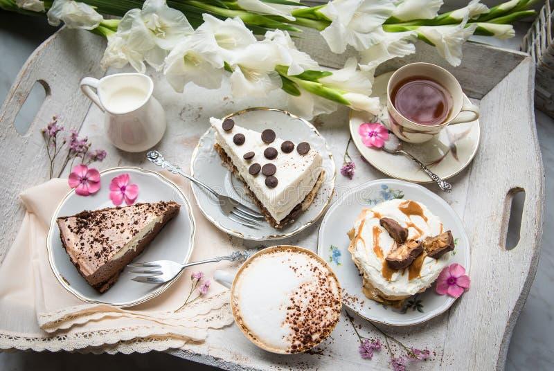 与咖啡、蛋糕、杯形蛋糕、点心、果子、花和新月形面包装载的表  库存照片