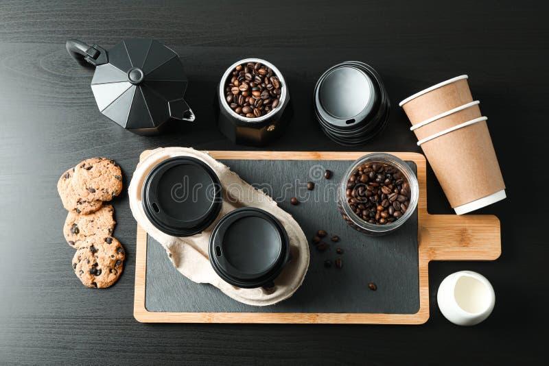 与咖啡时间辅助部件的平的被放置的构成在黑桌,文本的空间上 库存图片