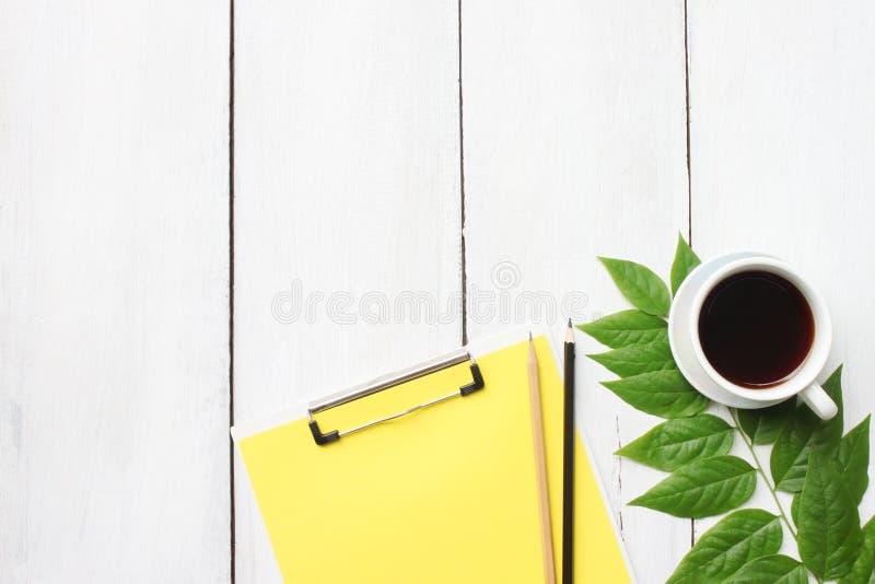 与咖啡杯、铅笔和fil的顶视图白色木书桌桌 免版税库存图片