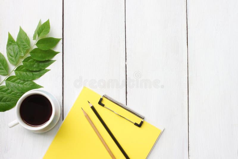 与咖啡杯、铅笔和fil的顶视图白色木书桌桌 库存图片