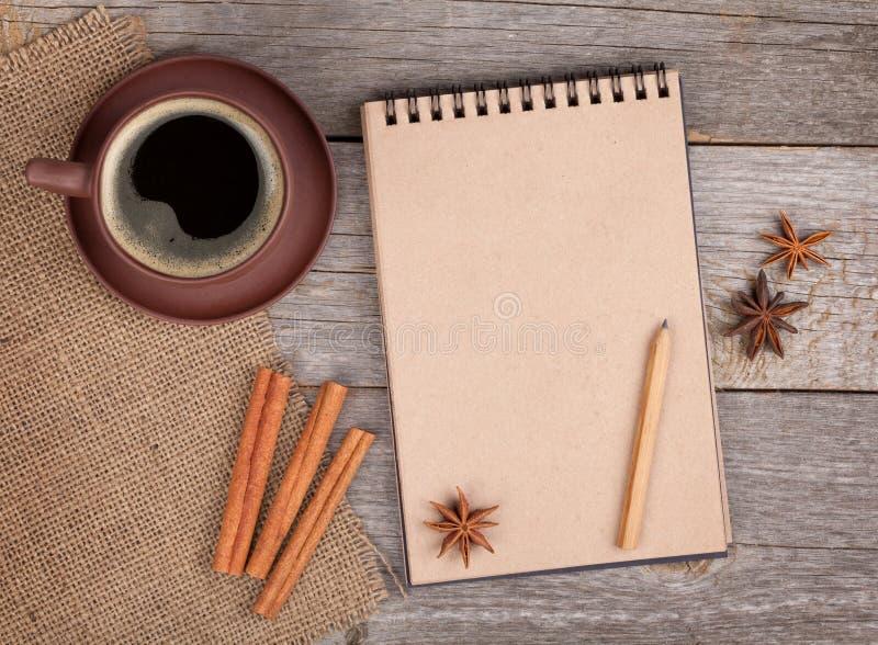 与咖啡杯和香料的空白的笔记薄在木桌上 免版税图库摄影