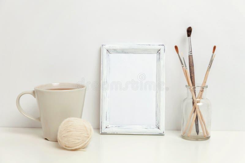 与咖啡杯的垂直的框架大模型在白色墙壁附近 免版税库存图片