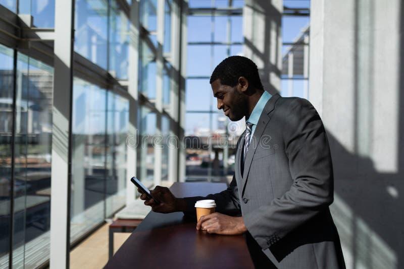 与咖啡杯的非裔美国人的商人使用手机在办公室 库存照片