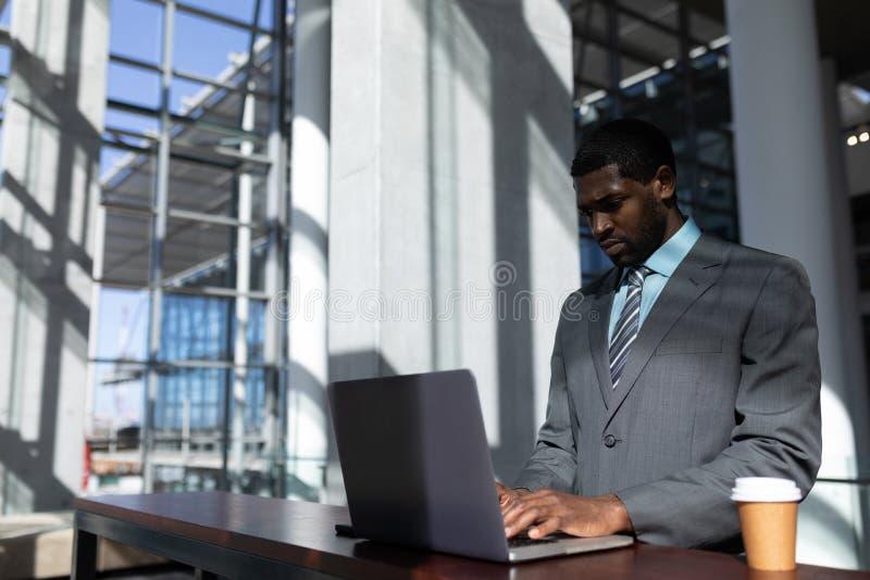 与咖啡杯的非裔美国人的商人使用膝上型计算机在办公室 库存图片