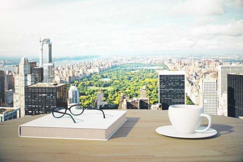 与咖啡的巨大城市视图、书和玻璃 库存图片