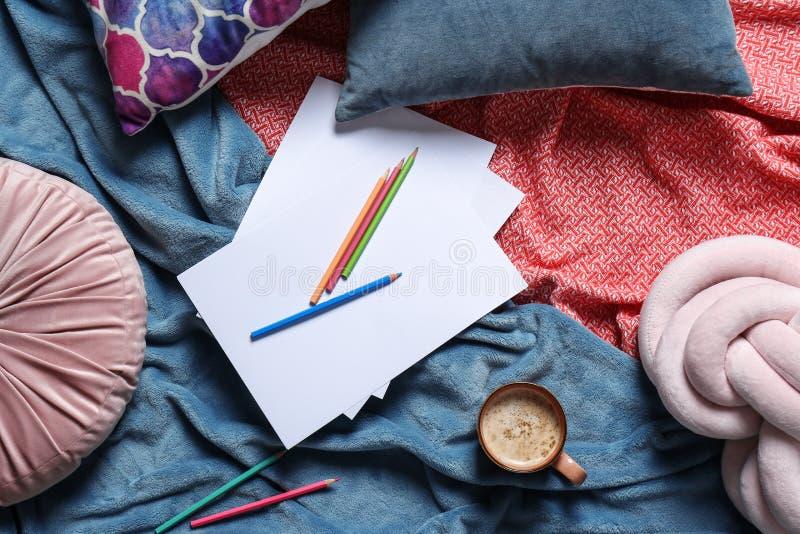 与咖啡的平的被放置的构成、铅笔、枕头和格子花呢披肩 免版税库存照片
