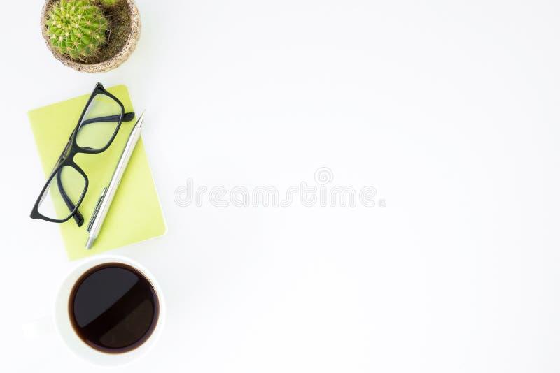 与咖啡的白色办公桌桌、笔记本和供应 r 免版税库存照片