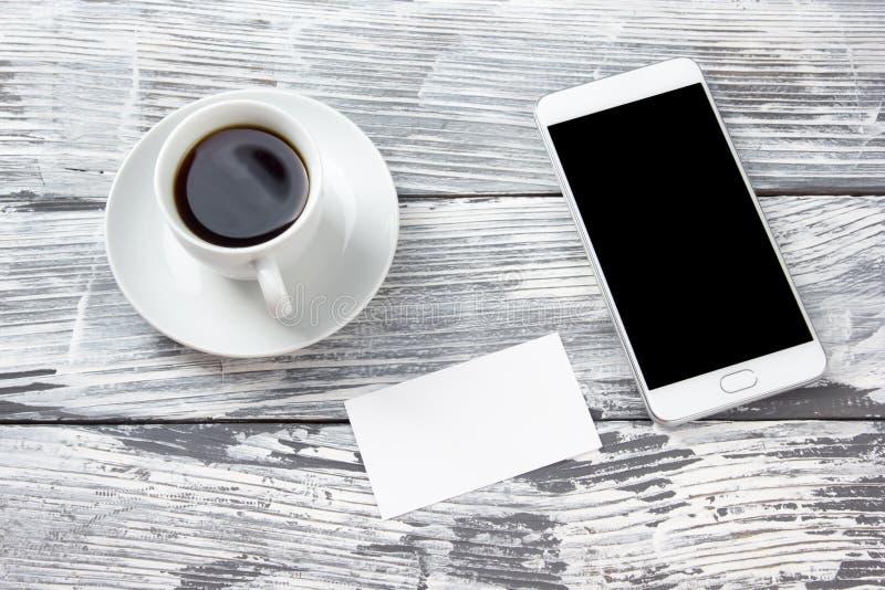 与咖啡的空白的事务卡片和片剂在木难看的东西办公桌桌上的个人计算机智能手机 复制您的空间 库存图片