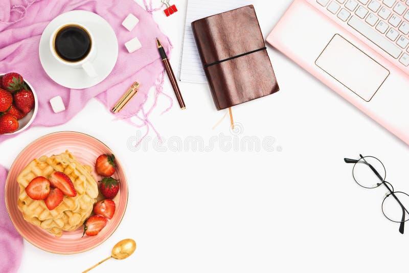 与咖啡的美好的flatlay安排、热的奶蛋烘饼与奶油和草莓,膝上型计算机和其它事项辅助部件 免版税库存照片