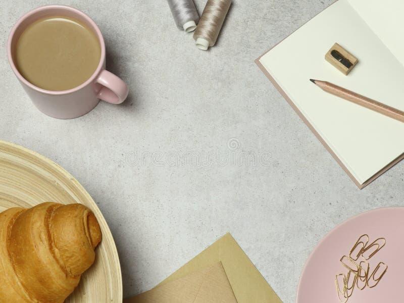 与咖啡的花岗岩背景和新月形面包,笔记,信封,夹子,螺纹 免版税图库摄影