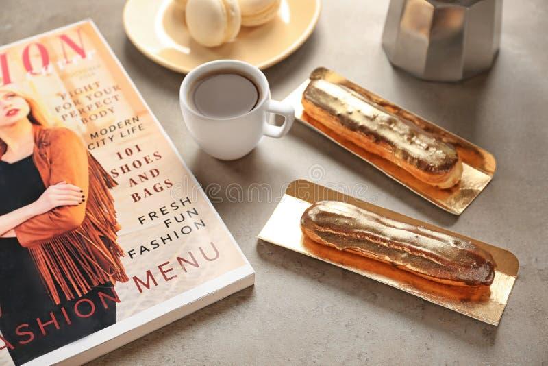 与咖啡的鲜美小饼和杂志在灰色桌上 免版税库存照片