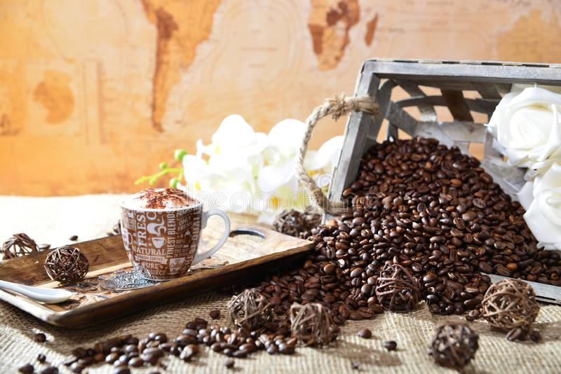 与咖啡豆和世界地图的热奶咖啡 免版税库存照片