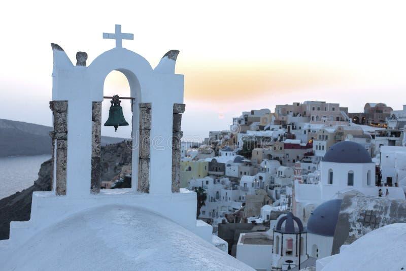 与响铃、白色房子和教会有蓝色圆顶的在Oia或Ia的曲拱在金黄日落,海岛圣托里尼,希腊 - Immagine 免版税库存图片