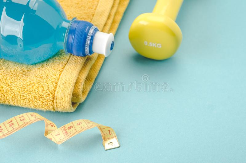 与哑铃、毛巾、措施磁带和瓶/黄色哑铃、毛巾、措施磁带和瓶的健身概念在蓝色 库存照片