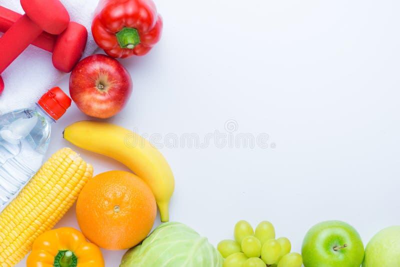 与哑铃和新鲜水果的健身框架 健康生活方式 免版税库存照片