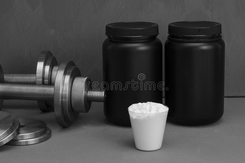 与哑铃的体育营养在灰色背景 免版税库存照片